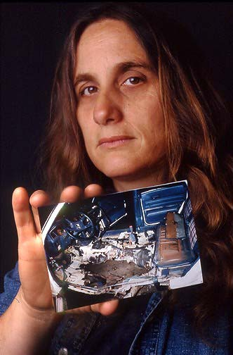 Judi Bari shows police photo of her bombed car, proving that the bomb was directly below her driver's seat